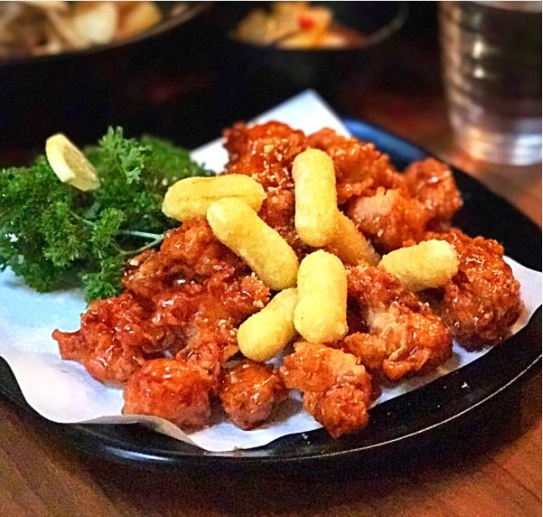 Image of spicy dakgangjung, which is boneless fried chicken and fried tteokbokki coated with a sweet, tangy and spicy sauce at Twins Korean Restaurant